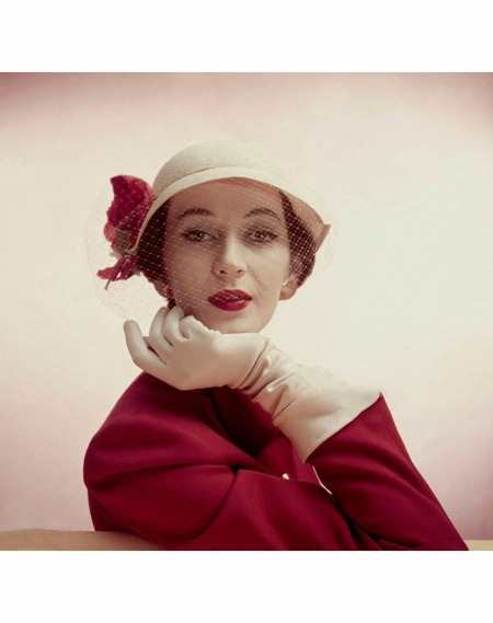 Model wearing brow-shading bonnet of pale straw with a side blaze of poppies and poppy-colored jacket Glamour 1950 © Clifford Coffin
