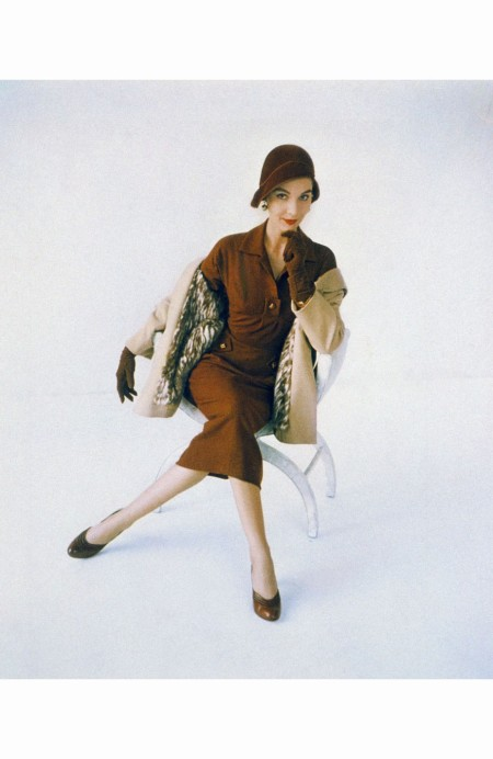 Model wearing topaz-colored dress and hat by Hattie Carnegie, gloves by Superb, a short pale topcoat lined with mink bellies, and Delmanette shoes horst-p-horst-vogue-september-1952
