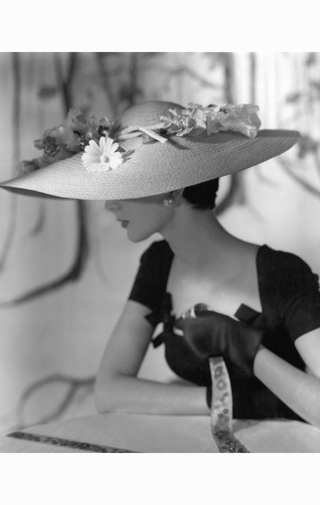 Model wearing wide-brimmed straw hat with flowers by Hattie Carnegie, with black dress and gloves horst-p-horst-vogue-march-1954
