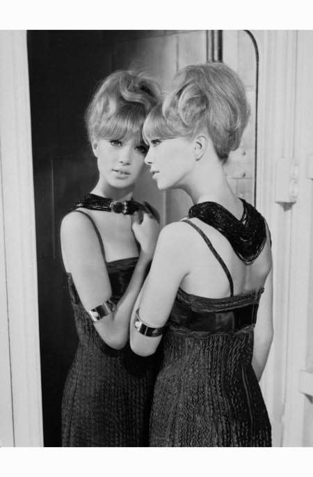 Patti Boyd in a bare-shouldered evening dress and an elaborate bead necklace leans wistfully against a full-length mirror 1964