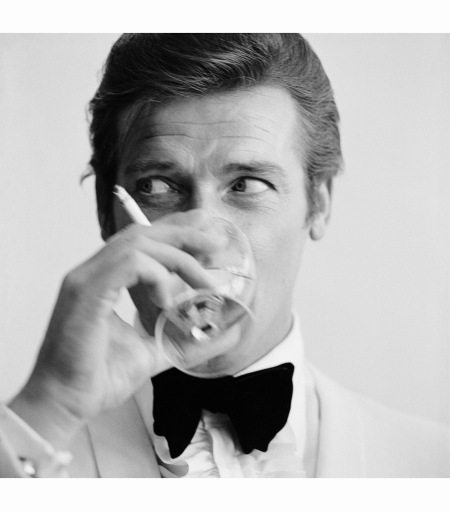 Roger Moore, well known for his roles as James Bond and the Saint, downs a martini. 1968 (Photo by Peter Ruck:BIPs:Getty Images)