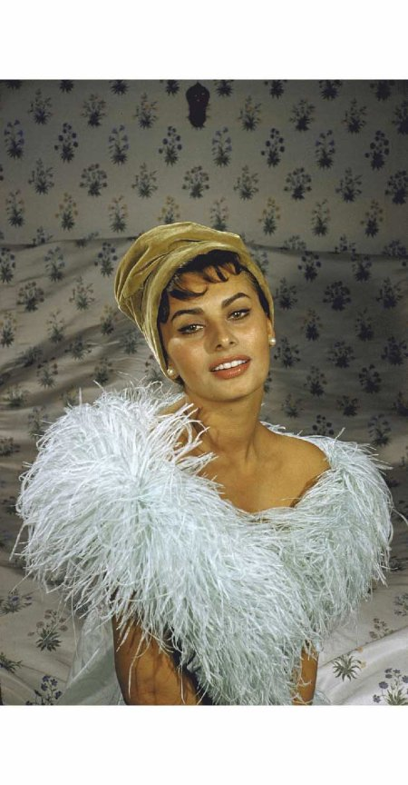 Sophia Loren wearing a cloche hat and feather boa posing in her bedroom 1957 Loomis Dean