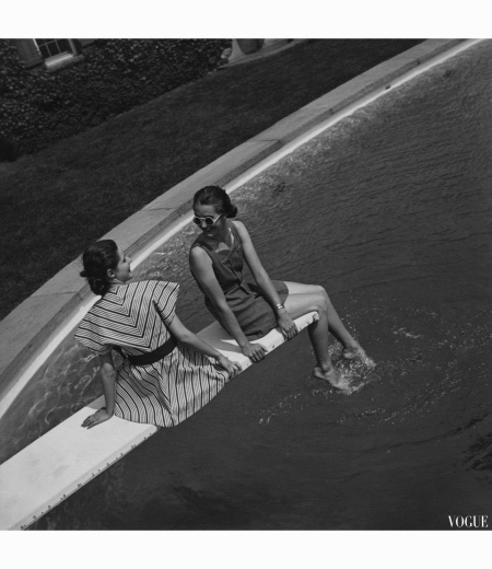 Two models sitting on a diving board, and wearing, left to right a flared tunic with chevron stripes and a stitched, blue denim bathing suit with white jersey shorts toni-frissell-vogue-july-1936