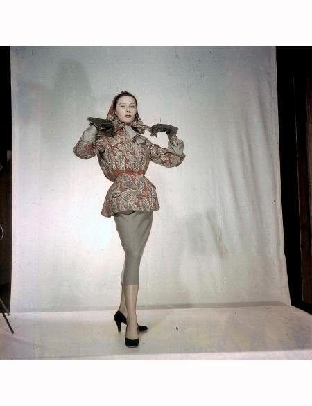 Women's Collections Spring 1951 By Fashion Designers Of Paris Bettina Maggy ROUFF, un ensemble veste jupe en lainage, à la veste resserrée à la taille, imprimée de motifs cachemire, avec un foulard assorti porté sur la tête