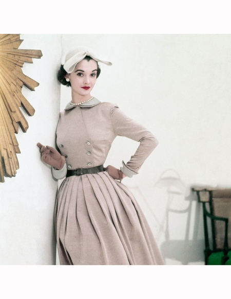 Model, in beige Sirrey Classics dress with grey linen collar and cuffs and John Frederics' Charmer hat, leans against wall with edge of gilt sunburst clock in foreground