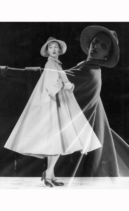 Double image of model wearing very full coat & wide brimmed hat; twirling to show drape of coat. Circa 1946 Gjon Mili