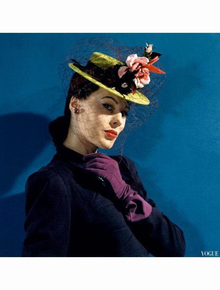 Model in chartreuse felt hat with roses and hummingbirds, purple gloves, and purple veil and ribbons Vogue 1941 b