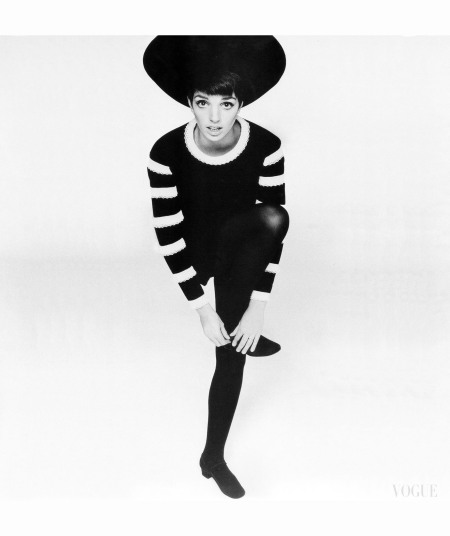 liza-minnelli-standing-on-one-leg-wearing-a-black-velvet-pancake-hat-by-halston-and-a-black-velvet-tunic-dress-with-white-eyelet-bands-on-the-sleeves-and-neckline-vogue-1967-alexis-waldeck