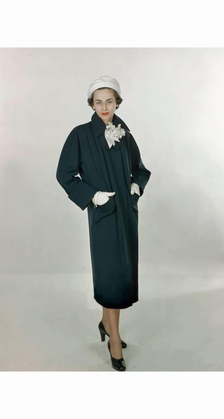 model-wearing-navy-worsted-wool-coat-by-lassie-maid-and-madcaps-pique-hat-in-white-glamour-1948-serge-balkin