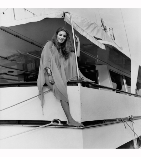 mrs-eugene-paul-getty-jr-wearing-a-chiffon-poncho-with-tassels-on-corners-she-is-seated-on-the-edge-of-the-yacht-antinoo-belonging-to-baron-and-baroness-arndt-krupp-von-bohlen-vogue-1970-p
