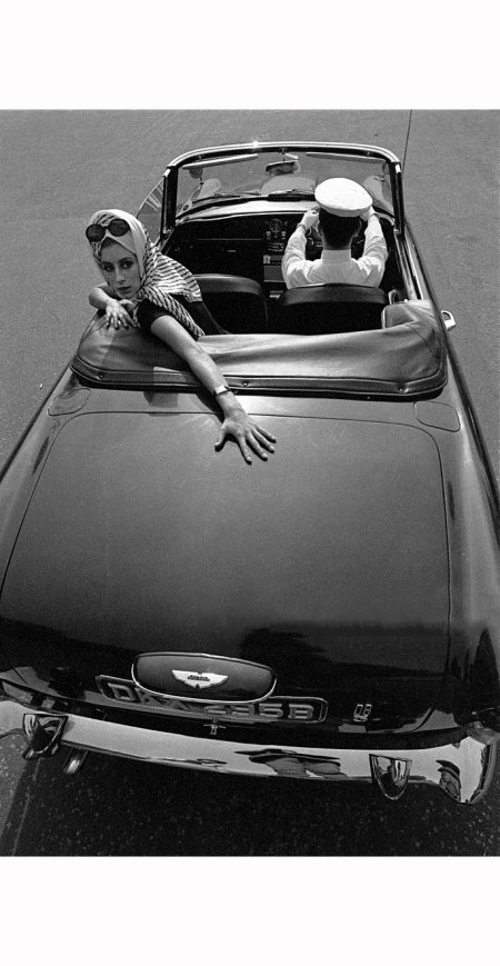 a-fashionably-dressed-young-woman-with-her-chauffeur-in-an-e-type-jaguar-sports-car-1965-b