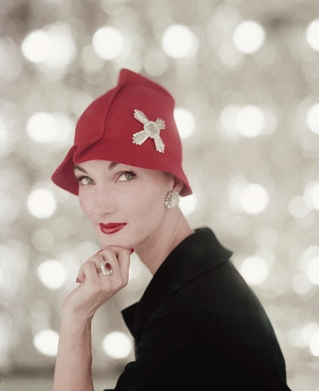 Evelyn Tripp wearing red felt hat with diamond Maltese cross, diamond earrings and diamond-and-ruby ring by Harry Winston Vogue Feb 1956 © Karen Radkai