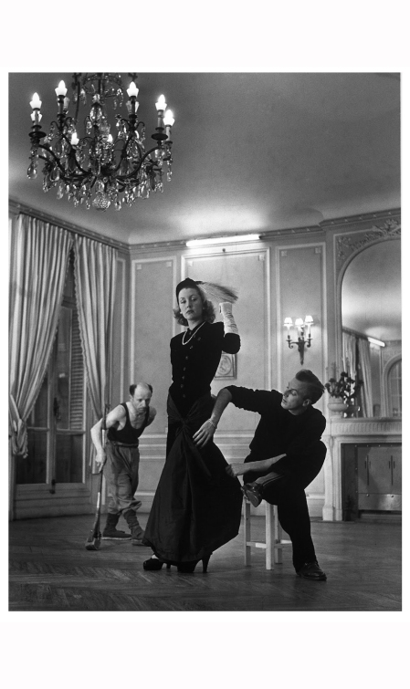 famous-couturier-jacques-fath-adjusting-one-of-his-evening-gowns-on-his-wife-before-paris-showing-while-a-floor-polisher-works-busily-in-the-bkgd