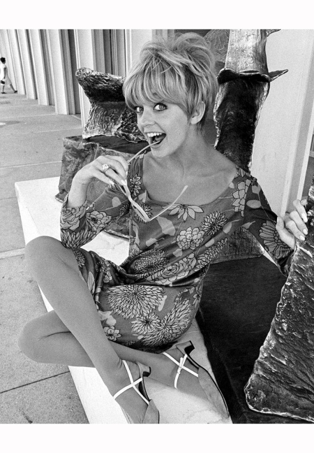 goldie-hawn-as-she-sits-legs-crossed-and-playfully-holds-a-pair-of-sunglasses-to-her-mouth-july-18-1967-photo-by-cbs-photo-archivegetty-images-b