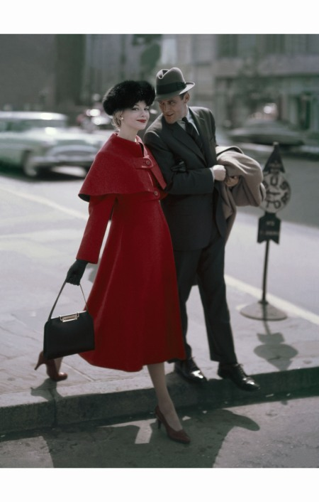 gretchen-harris-walking-on-street-with-man-wearing-crimson-coat-with-high-waist-buttoned-on-cape-by-young-couture-fox-hat-by-emme-purse-by-kore-glamour-september-1956-sante-forlano-bm