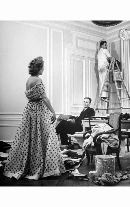pierre-balmain-c-observing-the-young-lady-modelling-an-evening-dress-designed-by-him-1951-nina-leen