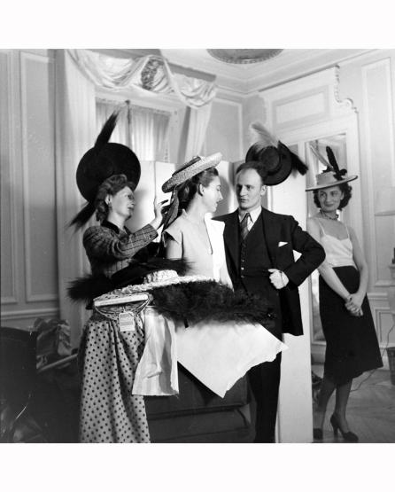 pierre-balmain-observing-modelling-an-evening-dress-designed-by-him-1951-nina-leen