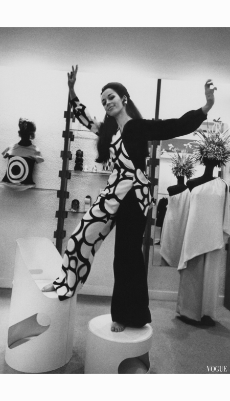 florence-grinda-stands-on-some-furniture-wearing-a-asymetrical-jumpsuit-pyjamas-in-the-simonetta-paris-boutique-vogue-april-1969-arnaud-de-rosnay