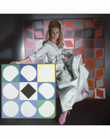 look-man-like-at-home-model-surrounded-by-artworks-by-vasarely-wearing-staron-silk-matelasse-evening-robe-by-stella-earrings-by-robert-originals-ring-by-fabiola-and-sandals-by-i-miller-hair-by-sug