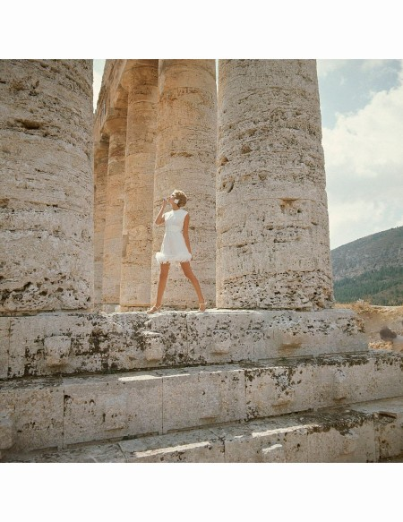 standing-among-the-giant-doric-pillars-of-segesta-in-sicily-wearing-white-crepe-culottes-edged-in-feathers-by-teal-traina-made-with-avisco-acetate-and-rayon-bloomsburg-fabric-e-ring-earrings-grip