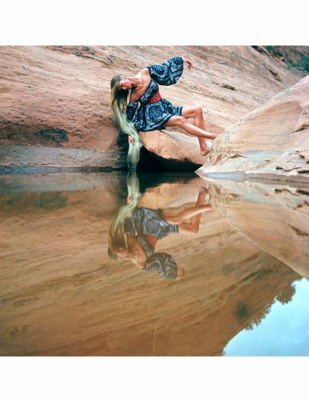 veruschka-leaning-over-a-pool-of-water-in-the-arizona-desert-wearing-a-blue-bandanna-print-dress-with-a-red-bandanna-around-her-waist-by-james-douglas-goodson