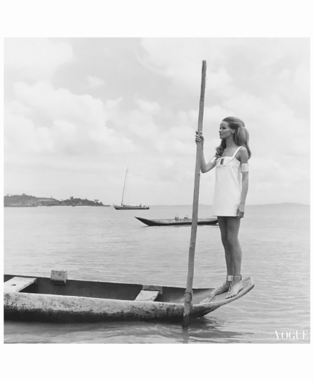 veruschka-wearing-white-denim-tube-shaped-minidress-with-narrow-shoulder-straps-square-cutout-at-bodice-flanked-by-two-triangular-tab-pockets-by-ginori-and-aluminum-armbands-and-sandals-with-ankle