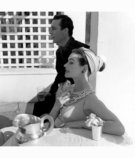 anne-gunning-parker-seated-wearing-twisted-headwrap-multicolored-beads-and-a-check-dress-and-holding-a-glass-to-her-chest-with-an-unidentified-man-horst-p-horst-vogue-may-1954-2