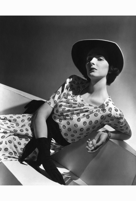 betty-mclauchlen-wearing-a-short-sleeved-white-crepe-dress-with-small-black-curlicues-print-a-black-cummerbund-two-clips-on-the-neckline-and-a-wide-brimmed-hat-with-white-trim-by-jay-thorpe-horst