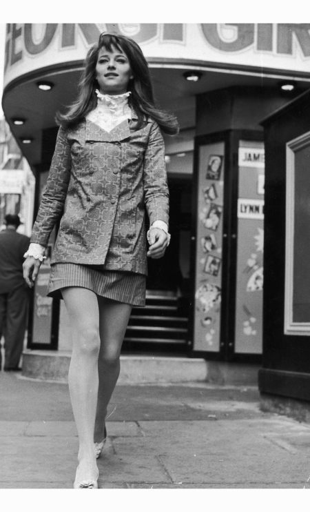 charlotte-rampling-wears-a-high-collared-edwardian-style-shirt-under-a-double-breasted-jacket-her-mini-skirt-is-in-contrasting-stripes-richard-chowen