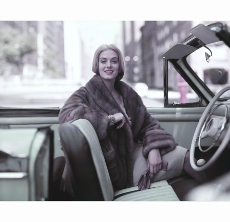 model-wearing-fur-coat-seated-in-a-convertible-holding-gloves