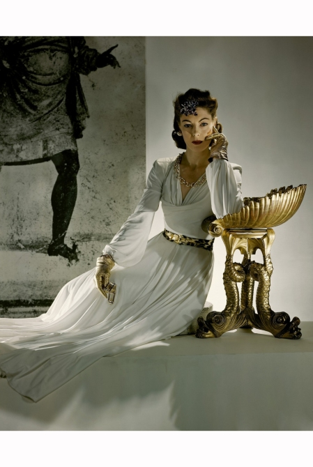 model-with-elbow-on-prop-in-front-of-mural-wearing-celanese-jersey-with-white-and-gold-trim-gold-kid-gloves-and-gold-and-amethyst-jewel-horst-p-horst-vogue-november-1940