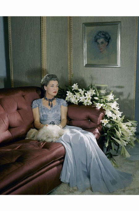 mrs-harrison-williams-aka-mona-bismark-in-evening-gown-wearing-jewelry-sitting-on-couch-with-pet-dog-in-her-lap-and-a-spray-of-lilies-to-the-left-her-portrait-hangs-in-the-background-horst-p-hors