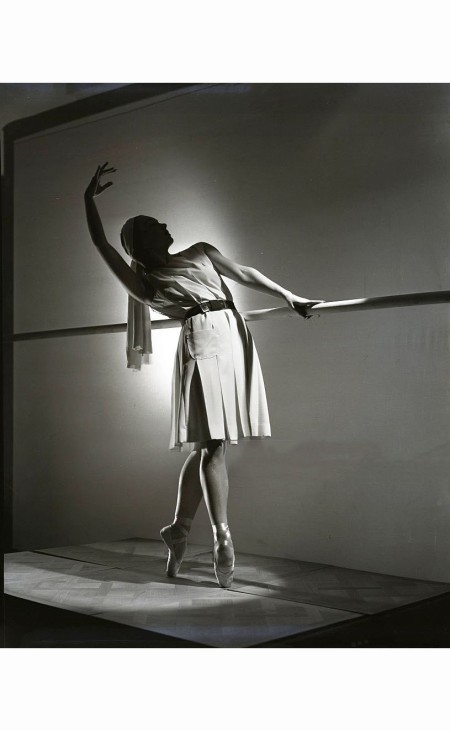 prima-ballerina-irina-baronova-wearing-play-dress-of-rayon-standing-at-a-barre-horst-p-horst