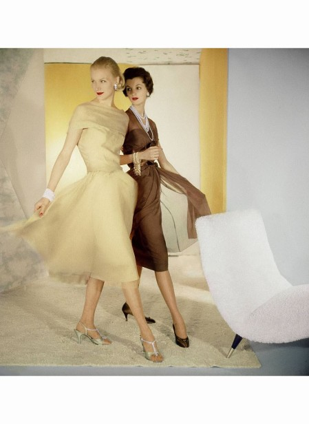 two-models-in-stride-sunny-harnett-left-in-beige-chiffon-dress-cut-softly-over-the-shoulder-with-long-bodice-and-skirt-cut-on-the-bias-other-wearing-brown-chiffon-dress-twice-banded-around-the-bodi