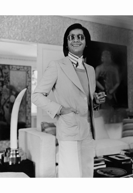 valentino-holding-a-cigarette-while-standing-in-the-living-room-of-his-via-appia-antica-home-near-rome-wearing-a-checked-blazer-sweater-striped-shirt-tie-white-pants-and-large-sunglasses-horst-p