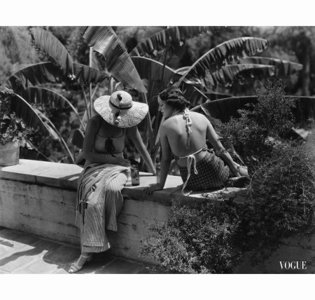 barbara-lee-wearing-striped-sudanette-pique-pajamas-and-phylis-cooper-wearing-patterned-pique-halter-playsuit-seated-on-ledge-from-left-in-california-vogue-july-1934-george-hoyningen-huene