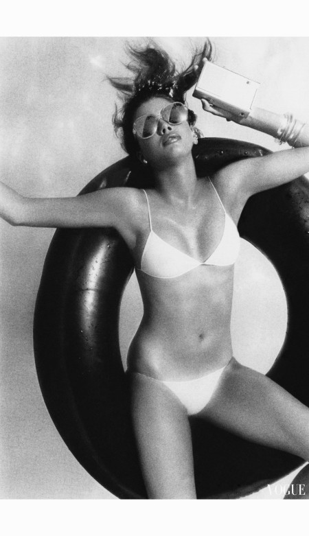janice-dickinson-floating-on-an-inner-tube-holding-a-small-radio-to-her-ear-and-wearing-a-triangular-string-bikini-in-white-cotton-knit-by-fiorucci-with-dark-sunglasses-vogue-may-1977-alber