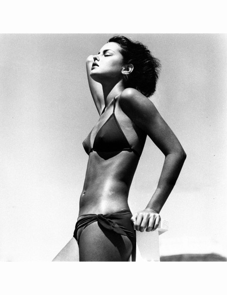 model-standing-against-a-wall-wearing-a-dark-bikini-with-sarong-tie-by-christian-dior-for-roxanne-albert-watson