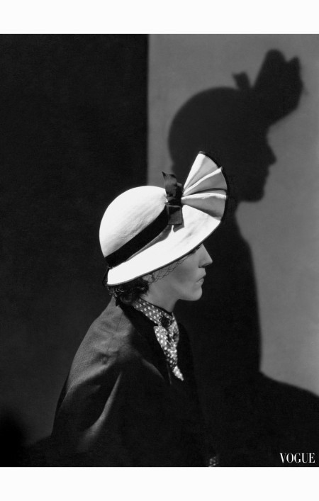 model-wearing-straw-poke-hat-with-fluted-peaked-brim-and-band-by-j-suzanne-talbot-and-wool-serge-dress-and-cape-trimmed-with-polka-dot-silk-by-maggy-rouf-vogue-december-1934-george-hoyningen