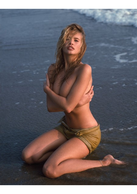 Claudia Schiffer on the beach during a photo shoot with photographer Herb Ritts