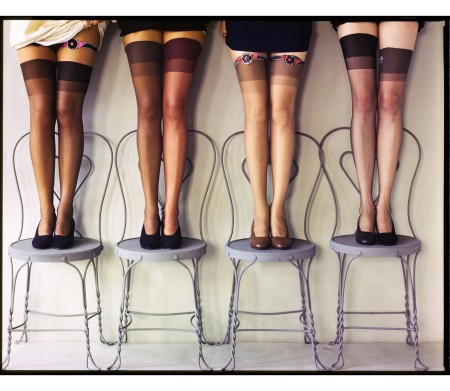 Models standing on cafe chairs displaying their stockings, published in Glamour, Dec. 1, 1947, issue © Herbert Matter
