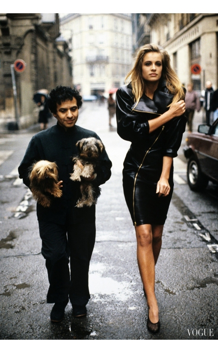 Azzedine Alaïa holding his two Yorkshire terriers,Patapouf and Wabo, walking in a Paris street with model Frederique van der Wal, Arthur Elgort, Vogue, February 1986