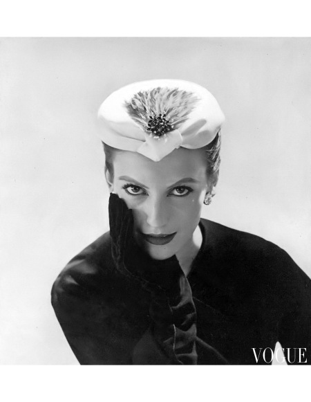 Mary Jane Russell is wearing a white satin toque with a lock of brilliant red feathers and a red jewelled pin by Balenciaga, photo by Horst, Vogue, October 15, 1953