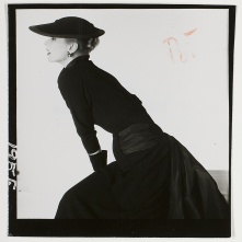 Model wearing black dress with wide pleated sash at waist, tied at back, c. 1951 e