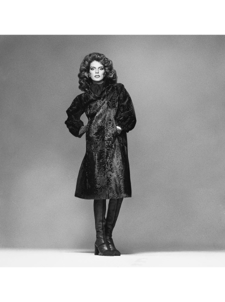 Rene Russo wearing a narrow, dark Swakara broadtail fur coat, by Givenchy, with a silk scarf and knee-high leather and suede boots Vogue 1974 © Francesco Scavullo