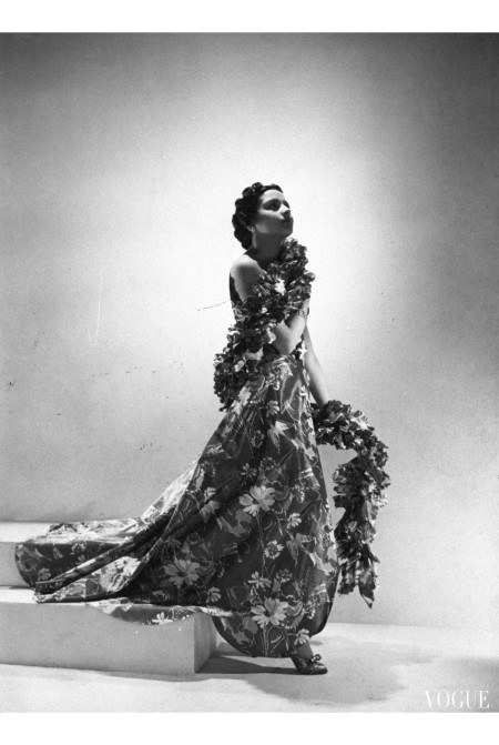 The Princess Karam of Kapurthala, back in Paris with a beautiful wardrobe of Mainbocher clothes—among them, this bird-and-flower-printed taffeta dress and boa of cut-out taffeta flower