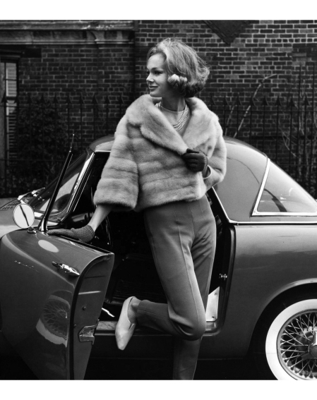 Anne de Zogheb modeling an EMBA mink jacket with pants, knit gloves, leather flats, and a necklace in front of a convertible. From the Young Tycoon Look series 1962