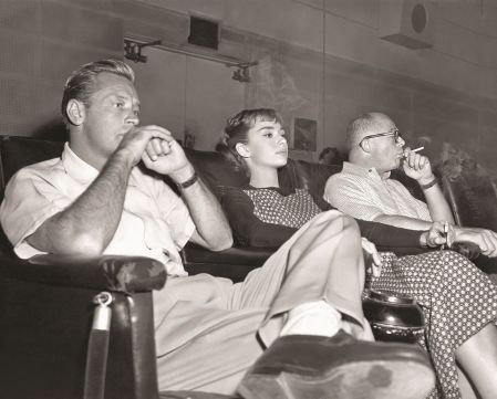 "Audrey Hepburn, William Holden and director Billy Wilder, photographed on set during a screening of ""Sabrina"" watching film in the Paramount screening room"