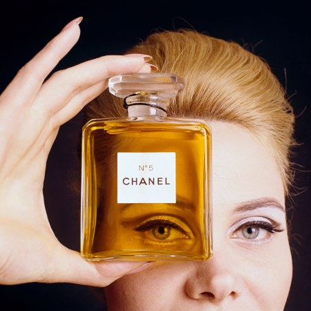 Close up of model holding a bottle of Chanel No. 5 Orange perfume up to her eye as if looking through the bottle Vogue 1964 © Fotiades:Condé Nast Getty Images