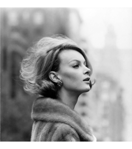 Monique Chevalier in profile, modeling a fur coat on Fifth Avenue, New York 1961